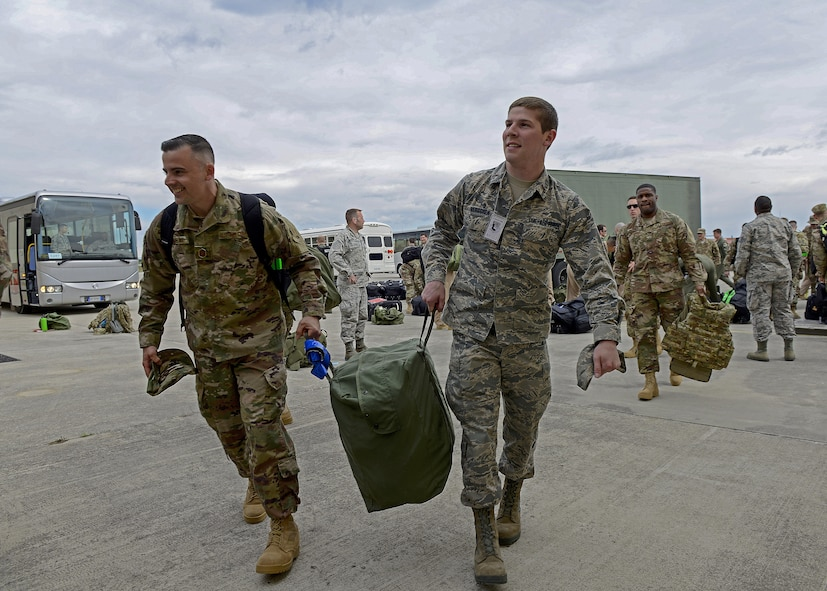 Master Sgt. Justin Mullins, 31st Aircraft Maintenance Squadron first sergeant, and 2nd Lt. Jacob Berggren, 31st Logistics Readiness Squadron assistant installation deployment officer, carry a deployment bag at Aviano Air Base, Italy, April 19, 2017. The 31st LRS assisted in deploying 344 service members from Aviano Air Base to Bagram Airfield. (U.S. Air Force photo by Airman 1st Class Ryan Brooks)