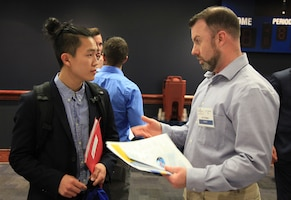 Mid-Atlantic Regional Maintenance Center (MARMC) Procurement Analyst Eric Dieges (right) speaks to an Old Dominion University (ODU) student about MARMC's Contracting Department during the ODU 2017 Spring Career Fair, Mar. 23. (Photo by Shelby West, Public Affairs Specialist)