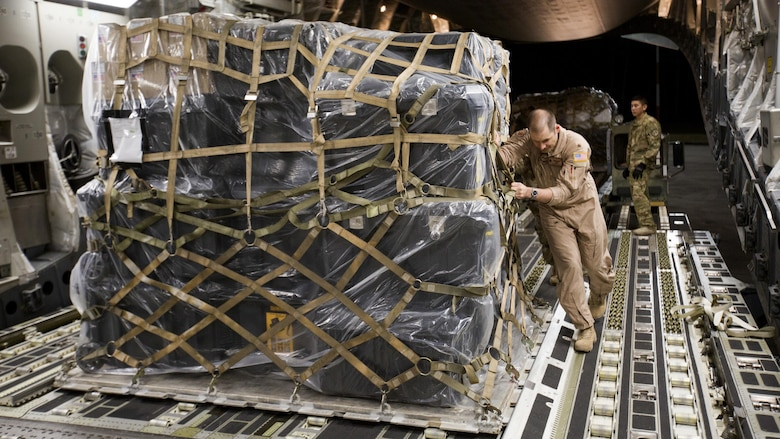 U.S. Air Force Maj. Robert Riggs, U.S. Marine Corps Forces, Special Operations Command air mobility liaison officer, assists in loading cargo aboard a C-17 aircraft at Marine Corps Air Station Cherry Point, North Carolina. As MARSOC's AMLO, Riggs provides a critical link of communication between the airlift and ground forces in the area of operations. He facilitated the mission from planning and coordination through hands-on facilitation by piloting the aircraft as it deployed and re-deployed two MARSOC units.