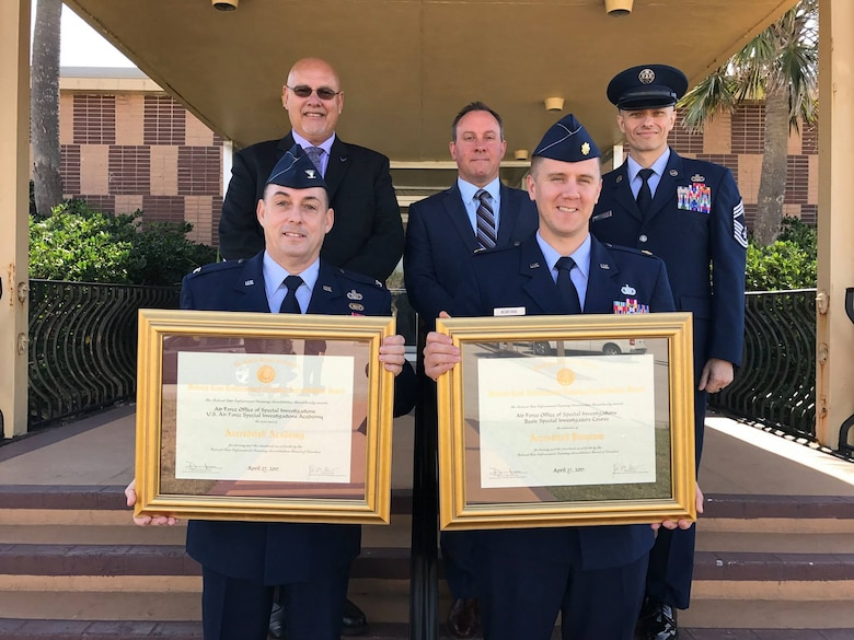 Col. Garry Little, AFSIA Commander, and Maj. Seth Newfang, AFSIA Chief, Basic Training Division, proudly show the reaccreditations AFSIA and the AFOSI Basic Investigators Course were granted by the Federal Law Enforcement Training Accreditation Board April 27, 2017. Joining them are, left to right, Mr. Dave Bynum, AFSIA Chief, Training Management Division, Mr. Greg Lynch, AFSIA Deputy Director and Chief Master Sgt. Gregory Carmack, AFSIA Superintendent. (AFSIA photo)