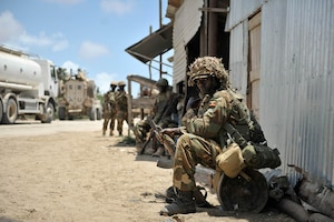 In 2014, a Ugandan soldier serving with AMISOM rests in advance of an AU and Somali National Force operation to liberate the Somali town of Barawe from the extremist group al-Shabaab.
