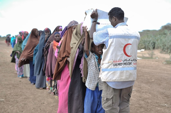 A young boy receives a box of food from a UAE Red Crescent employee at a distribution center in Somalia in August 2013. The UAE Red Crescent gave out food to more than 5,000 internally displaced persons aided in part by AMISOM forces.