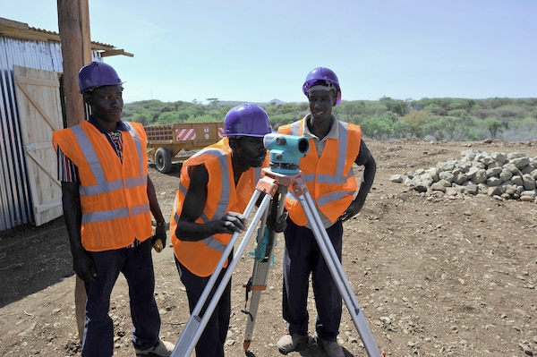 In 2014, water workers survey a biomass site in Kenya as part of the USAID Power Africa initiative.