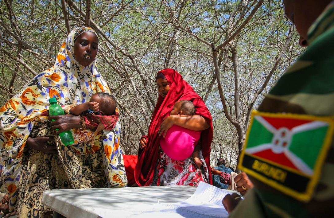 A female Burundian medical officer serving with the African Union Mission in Somalia (AMISOM) in 2013 speaks with Somali women at a free medical clinic in Mogadishu, where medical care was a lifeline for thousands of civilians who were caught up and injured during fighting with al-Shabaab. (Stuart Price/AMISOM posted by Albany Associates)