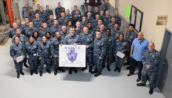 Commander, Navy Regional Maintenance Center Rear Adm. James P. Downey and MARMC Commanding Officer Daniel Lannamann pose with the most recent MARMC NAMTS graduating class. (Photo by Chris Wyatt, Public Affairs Specialist)