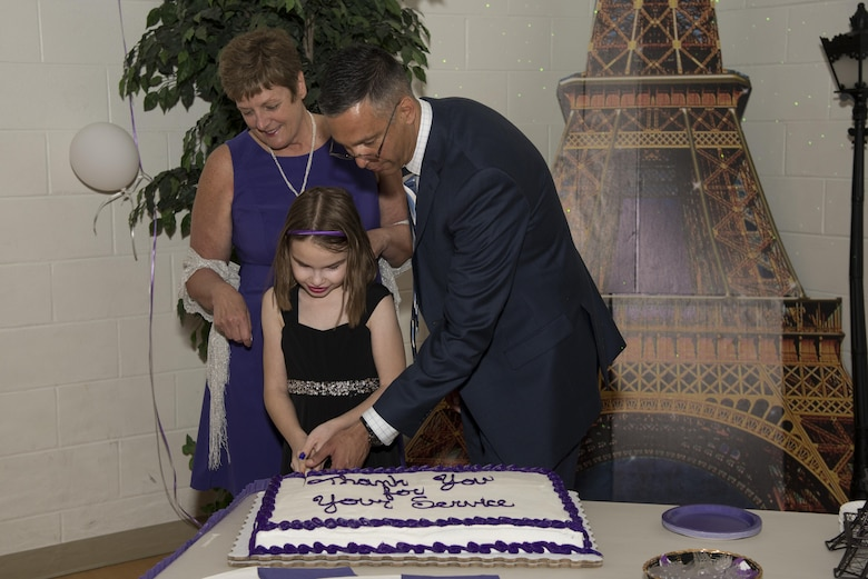 Karen Bradley, 436th Force Support Squadron Airman and Family Services flight chief, Col. Randy Boswell, 436th Mission Support Group commander, and Tory Ruhm, daughter of Staff Sgt. Michael Ruhm, 436th Maintenance Squadron crew chief, cut the cake during Team Dover's inaugural Purple Ball April 29, 2017, at the Youth Center on Dover Air Force Base, Del. The ball was organized to support military families during the Month of the Military Child, which is a commemorate month celebrated each April. (U.S. Air Force photo by Senior Airman Aaron J. Jenne)