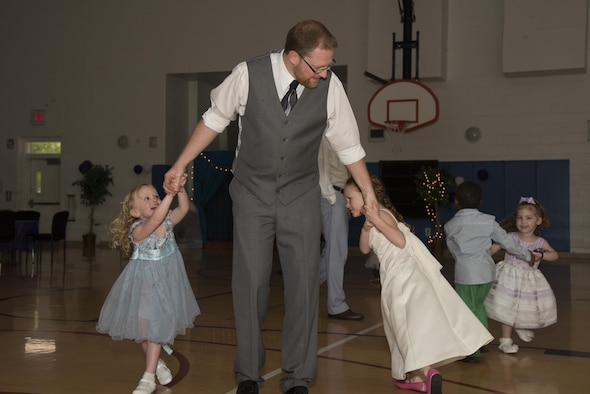 Joshua Pogge, 436th Maintenance Squadron aero repair craftsman, dances with his daughters, Cora and Lilly, during Team Dover's inaugural Purple Ball April 29, 2017, at the Youth Center on Dover Air Force Base, Del. Several families attended the formal event, which focused on the hardships military children endure and the challenges they overcome. (U.S. Air Force photo by Senior Airman Aaron J. Jenne)