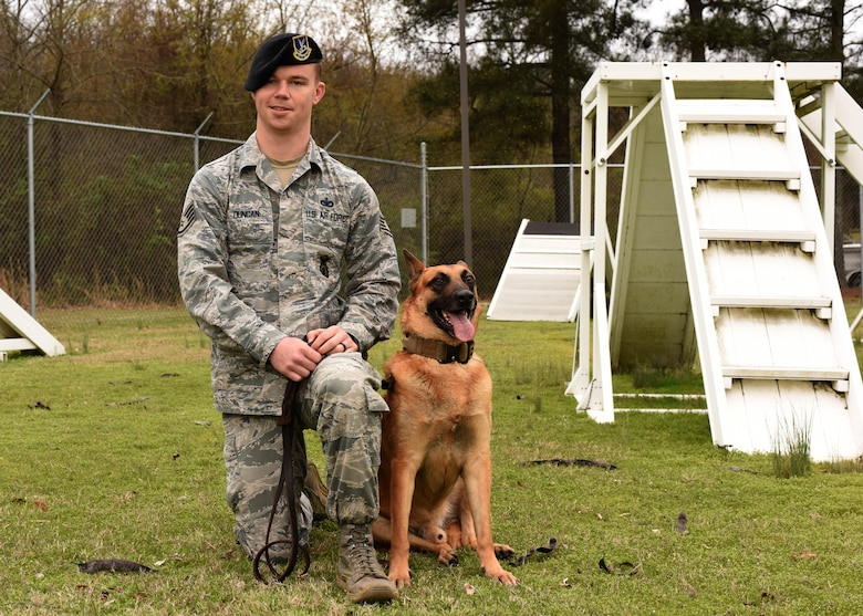 Staff Sgt. Tommy Duncan, 19th Security Forces Squadron K9 trainer, and Ricsi, retired military working dog, pose for a photo March 17, 2017, at Little Rock Air Force Base, Ark. Duncan adopted Ricsi after the dog retired in September 2016. (U.S. Air Force photo by Senior Airman Mercedes Taylor)