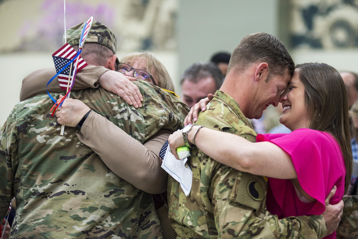 Two soldiers embrace loved ones as they return from deployment.