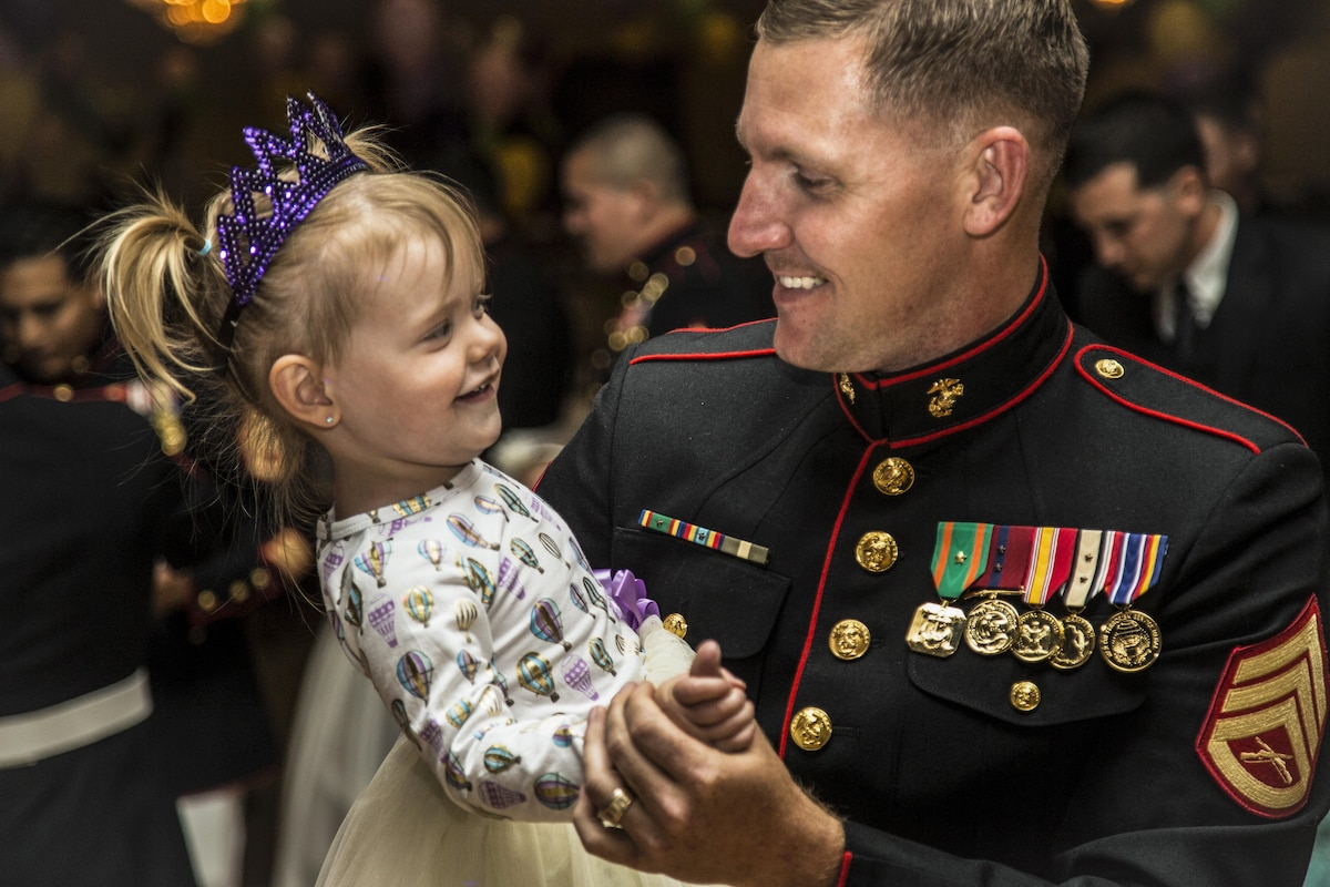 A Marine dances with his 2-year-old daughter at an event.