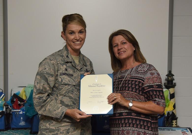 Col. Michele Edmondson, 81st Training Wing commander, presents Lisa Lyons, 81st Force Support Squadron community readiness specialist, with a Volunteer Excellence Award during the Annual Volunteer Recognition Ceremony in the Sablich Center April 27, 2017, on Keesler Air Force Base, Miss. The Volunteer Excellence Award is a lifetime achievement award recognizing volunteerism of a sustained and direct nature. The event recognized Keesler personnel, family member and retiree volunteers for their volunteer service in 2016. (U.S. Air Force photo by Kemberly Groue)