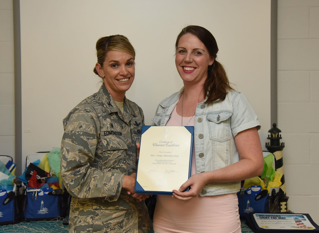 Col. Michele Edmondson, 81st Training Wing commander, presents Hope Blankenship, spouse of Master Sgt. Daniyel Blankenship, 81st Force Support Squadron readiness NCO in charge, with a Volunteer Excellence Award during the Annual Volunteer Recognition Ceremony in the Sablich Center April 27, 2017, on Keesler Air Force Base, Miss. The Volunteer Excellence Award is a lifetime achievement award recognizing volunteerism of a sustained and direct nature. The event recognized Keesler personnel, family member and retiree volunteers for their volunteer service in 2016. (U.S. Air Force photo by Kemberly Groue)