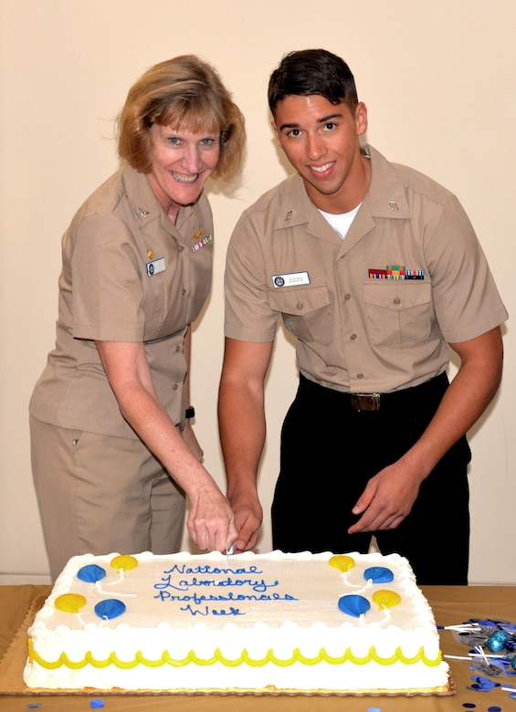 Naval Health Clinic Charleston Commanding Officer Capt. Elizabeth Maley, left, and Seaman Alex Zizzo, a NHCC laboratory technician, cut the cake during a ceremony celebrating Medical Laboratory Professionals Week April 25, 2017 at NHCC.