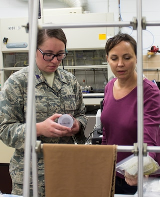 From left, U.S. Air Force Academy Cadet First Class Hayley Weir and AFCEC research chemist Katherine Simpson talk about Weir's capstone project; the development of a new ballistic resistant, flexible, lightweight nanotech-enabled fabric. The material, which is patent pending, could be applied as a protective lining on a variety of objects ranging from body armor to tents and vehicles. (U.S. Air Force photo/Mekka Parish)