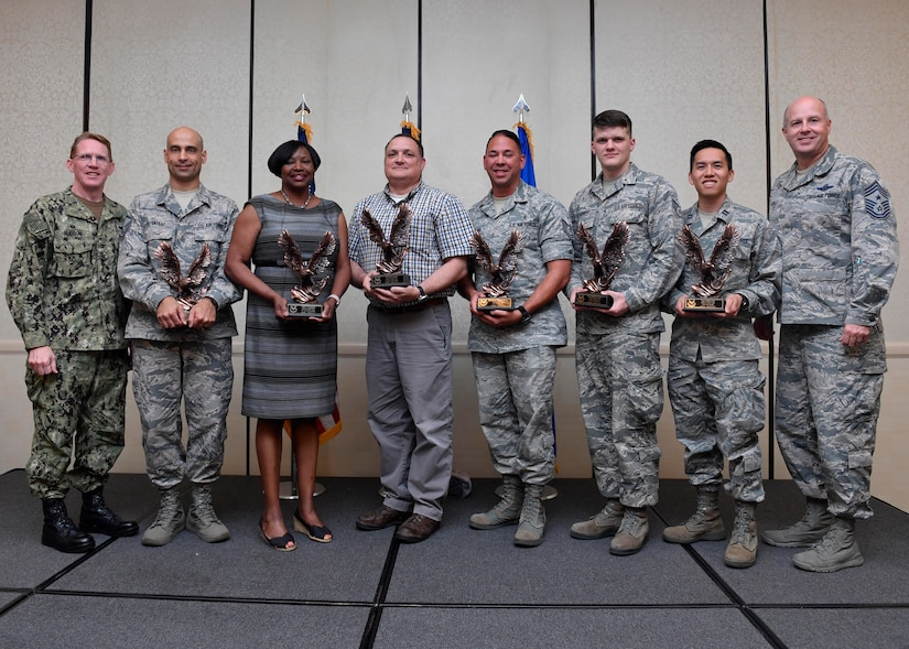 Members of Team Charleston are recognized by U.S. Navy Capt. Robert Hudson, left, Joint Base Charleston deputy commander, and Command Chief Master Sgt. Todd Cole, right, 628th Air Base Wing command chief, during the 628th ABW First-Quarter Awards Ceremony at the Charleston Club May 2, 2017, at Joint Base Charleston, S.C. Award winners were selected based on their ability to perform primary duties while adapting to military requirements.