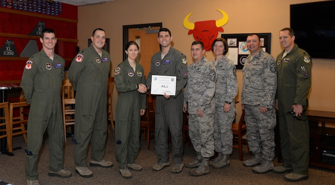"1st Lt. Jonathan Graziano, 87th Flying Training Squadron assistant flight commander (center), accepts the ""XLer of the Week"" award from Col. Michelle Pryor, 47th Flying Training Wing vice commander (left), and Chief Master Sgt. George Richey, 47th FTW command chief (right), on Laughlin Air Force Base, Texas, April 26, 2017. The XLer is a weekly award chosen by wing leadership and is presented to those who consistently make outstanding contributions to their unit and Laughlin. (U.S. Air Force photo/Airman 1st Class Daniel Hambor)"