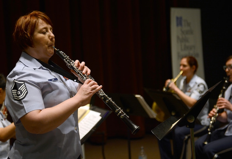 Master Sgt. Coreen Levin (center), Golden West Winds NCO in charge and oboe player, plays a song during the Golden West Winds performance at the Seattle Public Library, May 1, 2017 in Seattle, Wash. The members of the Golden West Winds are all professional Air force musicians working in support of Air Force and Air Mobility Command official military recruiting and community relations objectives. (U.S. Air Force photo/Senior Airman Divine Cox)