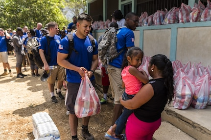 Villagers of San Jerónimo, Comayagua, Honduras receive bags of food from more than 190 members of Joint Task Force-Bravo to hiked approximately 3.6 miles round-trip to the village, Apr. 29, 2017. Members carried more than 5025 lbs of food and supplies, 24 soccer balls and 3 piñatas to the people of San Jerónimo. Chapel hikes have been occurring since 2003, with the JTF-Bravo Chapel sponsoring an average of six every year. The hikes are designed to provide a practical way for JTF-Bravo members to engage and partner with local communities to provide support to surrounding villages in need of food and supplies. (U.S. Air National Guard photo by Master Sgt. Scott Thompson/released)