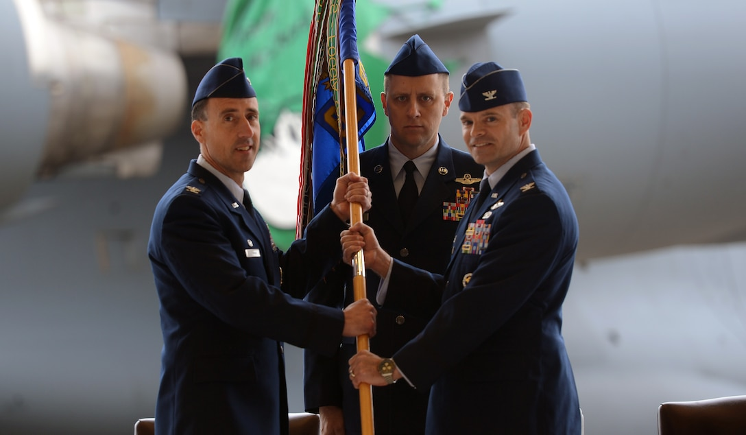 Col. Leonard Kosinski (left), passes a guidon to Col. Mark Fuhrmann, 62nd Operations Group commander, as Chief Master Sgt. Scott Mills (center), 62nd OG chief, stands at attention May 1, 2017, during a change of command ceremony at Joint Base Lewis-McChord, Wash.  Fuhrman took command from the outgoing commander Lt. Col. Brian Smith. (U.S. Air Force photo/Senior Airman Jacob Jimenez)