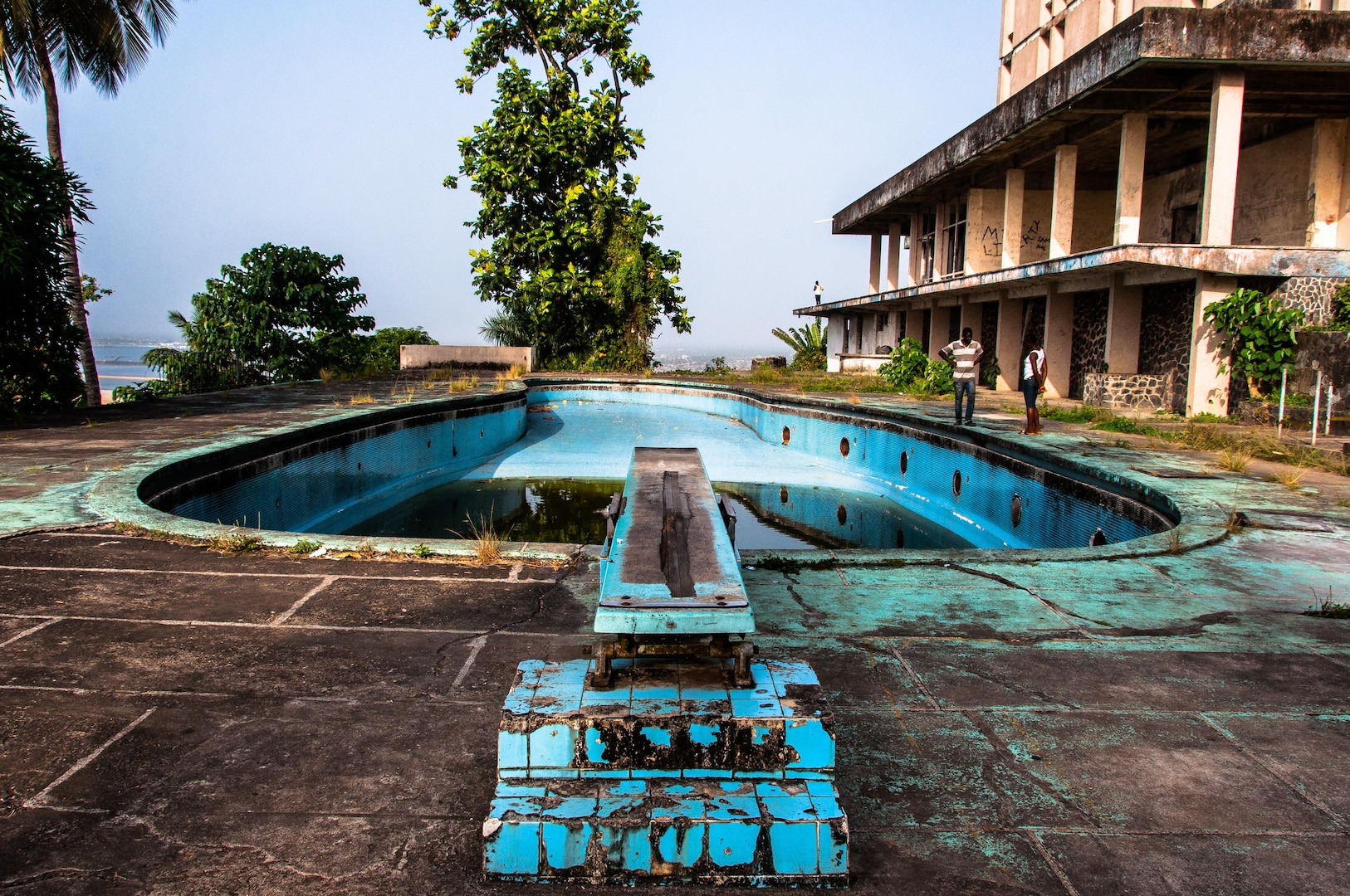 """The swimming pool area of the former Ducor Palace Hotel in Monrovia, Liberia.  The Ducor Palace Hotel in Monrovia was the first international-class hotel constructed in Liberia, and was for many years one of the few five-star hotels in all of Africa. It had three hundred rooms, a pool, tennis courts, and a French restaurant and was popular with tourists and businesspeople from Africa and around the world.  It sits on Ducor Hill and overlooks the Atlantic Ocean and the Saint Paul River.  The hotel closed in 1989, just before the First Liberian Civil War. The building was severely damaged by the violence of the war and the looting that occurred afterwards. During and after the war, displaced residents of many of Monrovia's slums began to occupy the hotel's empty rooms.  In 2007, the Liberian Ministry of Justice began to evict the Ducor Hotel's residents and in 2008, the Government of Liberia signed a lease agreement with the Government of Libya, who began clearing the property of debris in 2010 in preparation for a bidding process to be completed by June 2010. The project was delayed several times before finally being abandoned upon Liberia's severing of diplomatic relations with the Gaddafi government following the outbreak of the 2011 Libyan civil war.  The building is open today and visitors can walk throughout the grounds and building (often after paying a """"security fee"""" to have one of the guards accompany them).  It is a popular place for Monrovia residents to come and enjoy the panoramic view of the city, especially for special occasions like Christmas, New Years, and Independence Day."""