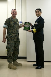 MCAS FUTENMA, OKINAWA, Japan – Lt. Col. Bob Sweginnis, left, receives a plaque from Capt. Hiroyuki Habuchi March 24 on Marine Corps Air Station Futenma, Okinawa, Japan. Officer candidates with the Japan Maritime Self-Defense Force visited the air station to learn about the cooperation between the Marines and Japan Self-Defense Force. Habuchi is the commander of the 1st Training Submarine Division, JMSDF. Sweginnis is the executive officer of MCAS Futenma. (U.S. Marine Corps photo by Cpl. Jessica Collins)