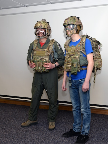 "U.S Air Force Lt Col. Jason Barnes, left, 351st Air Refueling Squadron commander, and his son Ian, 13, pose for a photo after being dressed in survival, evasion, resistance and escape gear during a demonstration at the ""Bring Your Child to Work Day"" for Month of the Military Child April 28, 2017, at the 100th Operations Group on RAF Mildenhall, England. In addition to hanging out with their parents at work, children had the opportunity to see a KC-135 Stratotanker close up, listen to some kid-friendly briefings, participate in physical training and take part in SERE training. (U.S. Air Force photo by Karen Abeyasekere)"