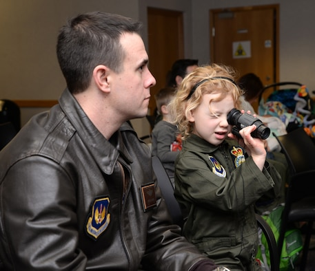 """U.S. Air Force Maj. Michael Harrison, left, 100th Operations Support Squadron assistant director of operations, listens to a survival, evasion, resistance and escape instructor as his daughter Isabella, 5, checks out a night-vision monocular at the 100th Operations Group """"Bring Your Child to Work Day"""" as part of Month of the Military Child April 28, 2017, on RAF Mildenhall, England. During the kid-friendly SERE training, children tried on equipment including helmets, and had their faces painted with camouflage pattern. (U.S. Air Force photo by Karen Abeyasekere)"""