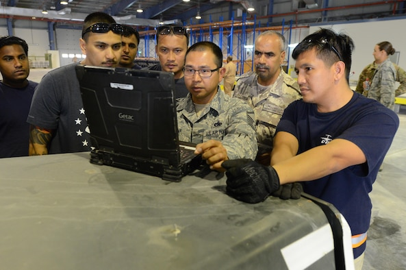 Qatari air force representatives look on as U.S. Air Force Master Sgt. Nino Lucena, Air Freight Superintendent assigned to the 8th Expeditionary Air Mobility Squadron, reviews pallet loading training orders on a lap top computer. The group is taking part in the first of many collaborative training exercises between U.S. Air Force and Qatari air force personnel. (U.S. Air Force photo by Tech. Sgt. Bradly A. Schneider)