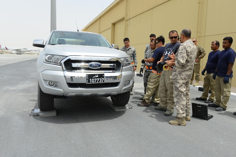 U.S. Air Force and Qatari air force personnel gather around a vehicle outside a newly constructed facility located at Al Udeid Air Base, Qatar, April 26, 2017. The personnel are taking part in the first of many opportunities to train on how to properly collect information necessary to determine the total weight and center of gravity for equipment to be loaded for transportation on aircraft. (U.S. Air Force photo by Tech. Sgt. Bradly A. Schneider)