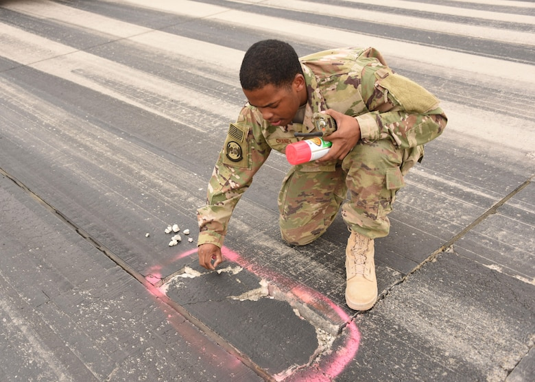 Senior Airman Jourdan Chaney, an airfield management specialist with the 386th Expeditionary Operations Support Squadron, identifies safety hazards on the runway at an undisclosed location in Southwest Asia, April 30, 2017. Airfield management specialists manage airfield operations to ensure a safe, effective, and efficient airfield environment. (U.S. Air Force photo/Tech. Sgt. Jonathan Hehnly)