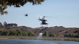 Helicopters fill up with water from Lake O'Neill to assist Camp Pendleton Firefighters during the Roblar Fire on Camp Pendleton, Calif., July 22, 2016. The Roblar Fire has burned 2,000 acres and currently at 30% containment.