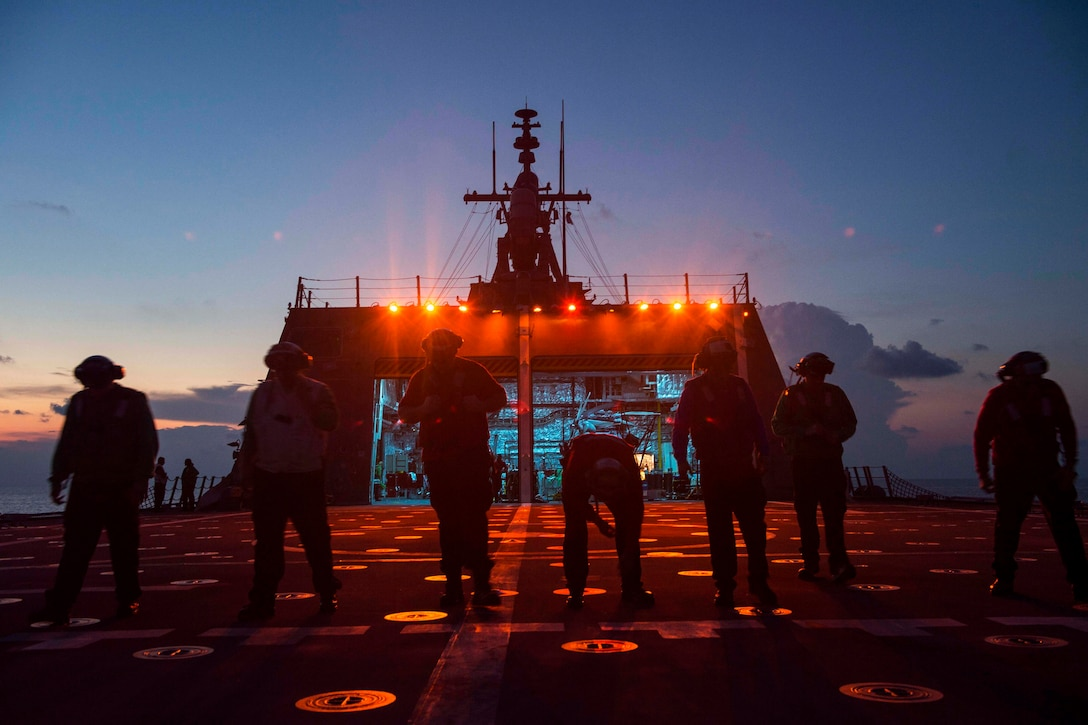 Sailors search for foreign object debris on the USS Coronado in the South China Sea.