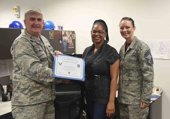 Melinda Forgit, 22nd Contracting Squadron contract specialist, poses with Col. Albert Miller, 22nd Air Refueling Wing commander, and Chief Master Sgt. Jamie Capps, 22nd Medical Group superintendent, April 21, 2017, at McConnell Air Force Base, Kan. Forgit received the spotlight performer for the week of April 10-14. (U.S. Air Force photo/Airman 1st Class Erin McClellan)