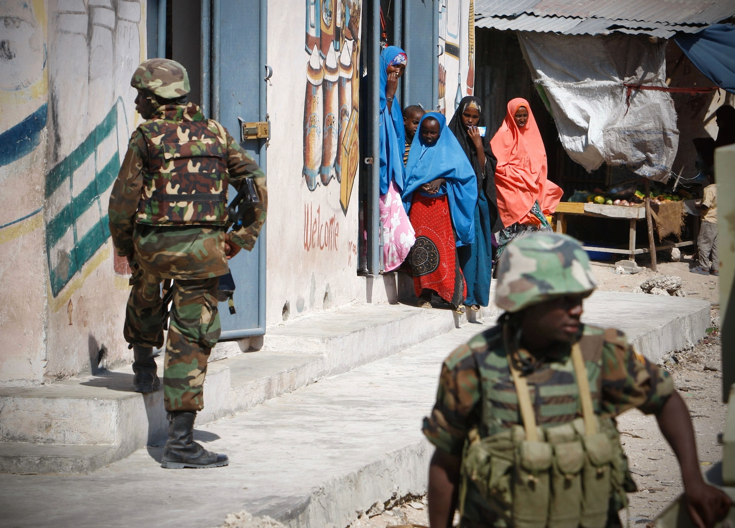 SOMALIA, Mogadishu: In a photograph taken 5 Dec and released by the African Union-United Nations Information Support Team 8 Dec, Somali women look on as Ugandan soldier serving with the African Union Mission in Somalia (AMISOM) take up defensive positions in Torfiq market in the Yaaqshid District of northern Mogadishu. In the face of a surge of car bombings and improvised explosive device (IED) attacks, the 9,700-strong African Union force continues to conduct security and counter-IED operations in and around the Somali capital. AU-UN IST PHOTO / STUART PRICE.