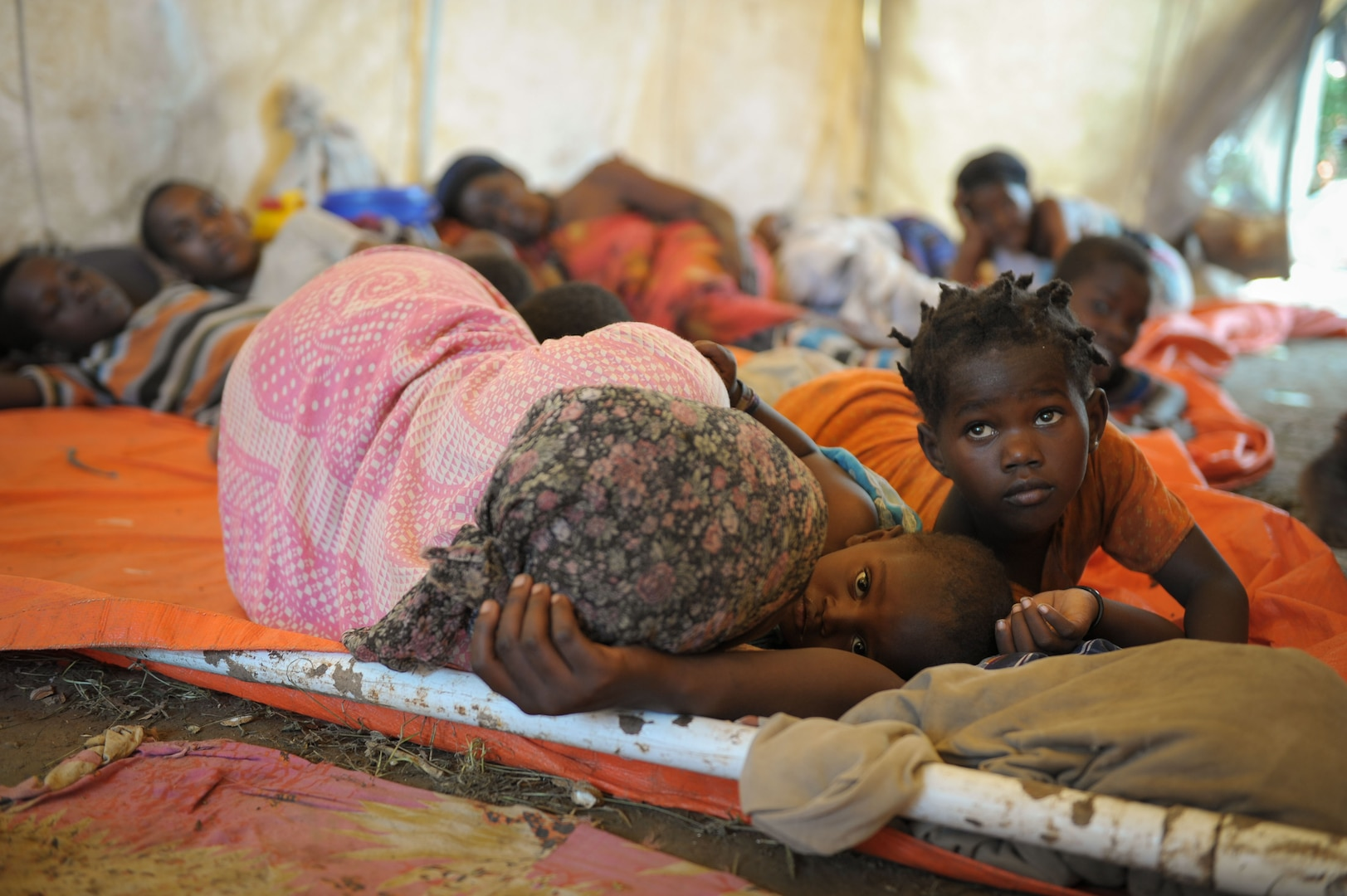 Women and children sleep in a makeshift hospital erected at an AMISOM military camp to help those affected by recent flooding and clan conflict near Jowhar, Somalia, on November 12. Heavy rains in Somalia, coupled with recent disputes between clans, has resulted in over four thousand IDPs seeking shelter at an AMISOM military base near the town of Jowhar, with more arriving daily. AU UN IST Photo / Tobin Jones