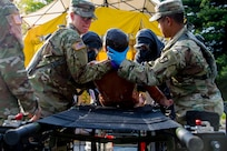 Spc. Megan Rowley (left) and Spc.  Kristopher Fernando medics assigned to the 602nd Area Support Medical Company located at Fort Bragg, N.C., move a scenario casualty from the decontamination area to a gurney for assessment April 29, 2017, as part of  Exercise Guardian Response at Muscatatuck Urban Training Center, Ind. Guardian Response is a multi-component training exercise run by the U.S. Army Reserve designed to validate more than 4,000 service members in Defense Support of Civil Authorities (DSCA) in the event of a Chemical, Biological, Radiological and Nuclear (CBRN) catastrophe. This year's exercise simulated an improvised nuclear device explosion with a source region electromagnetic pulse (SREMP) out to more than four miles. The 84th Training Command is the hosting organization for this exercise, with the training operations run by the 78th Training Division, headquartered in Joint Base McGuire-Dix-Lakehurst, New Jersey. (U.S. Army Reserve Photo by Maj. Adam Weece, 206th Broadcast Operations Detachment)