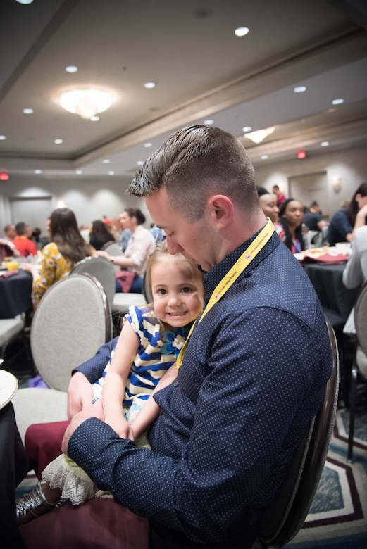 Staff Sgt. Timmothy Pettis, 916th Aircraft Maintenance Squadron crew chief holds his daughter Regan during a Yellow Ribbon program event in New Orleans, April 21-23. (U.S. Air Force photo by Staff Sgt. Heather Heiney)