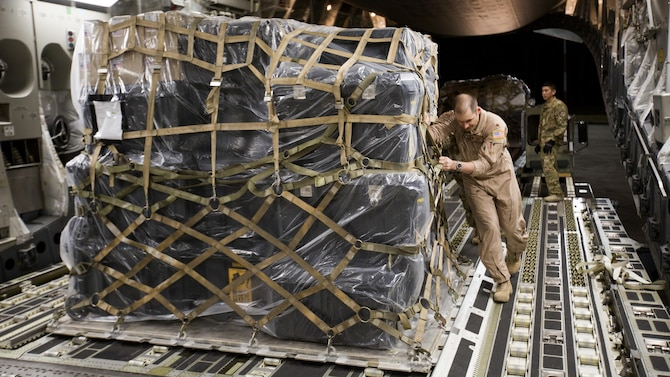 U.S. Air Force Maj. Robert Riggs, U.S. Marine Corps Forces, Special Operations Command air mobility liaison officer (AMLO), assists in loading cargo aboard a C-17 aircraft at MCAS Cherry Point. As MARSOC's AMLO, Riggs provides a critical link of communication between the airlift and ground forces in the area of operations. He facilitated the mission from planning and coordination through hands-on facilitation by piloting the aircraft as it deployed and re-deployed two MARSOC units. (U.S. Marine Corps photo by Sgt. Salvador Moreno, released)