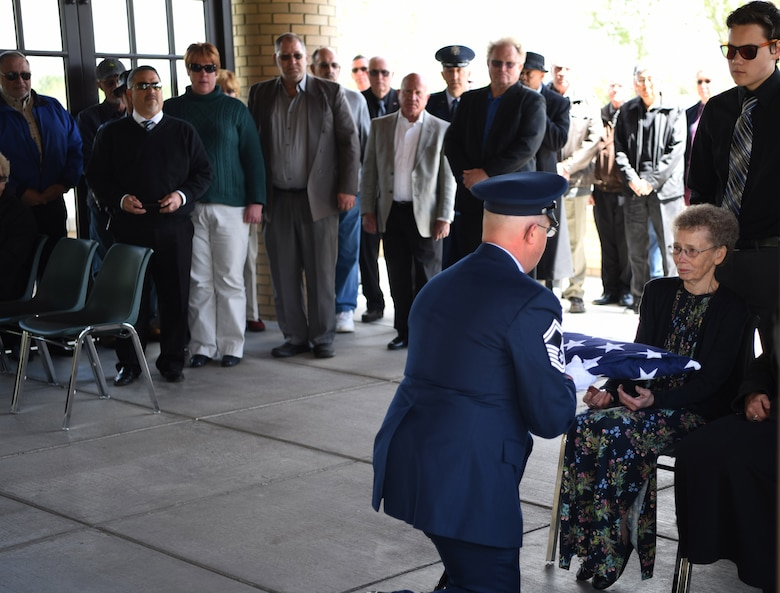 Senior Master Sgt. Brett Kitzman, 140th Maintenance Group aircraft armament systems superintendent, presents the tri-fold flag to the spouse of a deceased veteran, Apr. 28, 2017, at Fort Logan National Cemetery, Colo. Kitzman, who worked with the deceased in the past, volunteered to participate in the service and to present to tri-fold flag to the next of kin. (U.S. Air Force photo by Airman 1st Class Holden S. Faul/ released)
