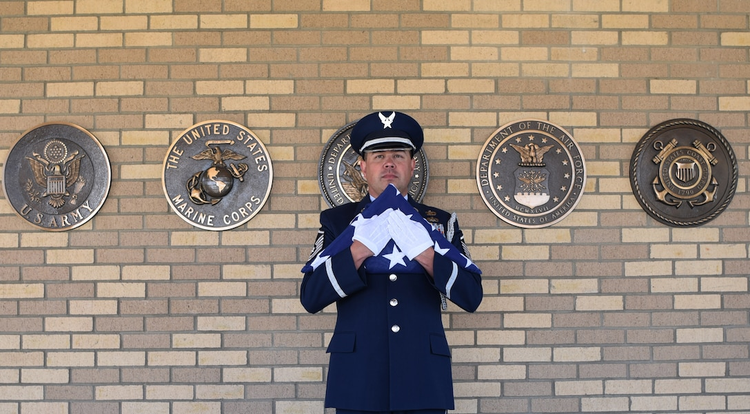 Master Sgt. Wolfram Stumpf, Mile High Honor Guard flight chief, stands with a tri-fold flag moments before presenting it to the spouse of deceased veteran, Apr. 28, 2017, at Fort Logan National Cemetery, Colo. Stumpf has been titled the 2016 Air Force Space Command Honor Guard member of the year, and is now up for the award at the Air Force level. (U.S. Air Force photo by Airman 1st Class Holden S. Faul/ released)