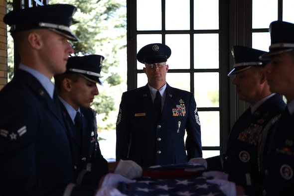 Senior Master Sgt. Brett Kitzman, 140th Maintenance Group aircraft armament systems superintendent, stands at attention while members of the Mile High Honor Guard fold the flag during a military funeral honor, Apr. 28, 2017, at Fort Logan National Cemetery, Colo. Kitzman, who worked with the deceased in the past, volunteered to participate in the service and to present to tri-fold flag to the next of kin. (U.S. Air Force photo by Airman 1st Class Holden S. Faul/ released)
