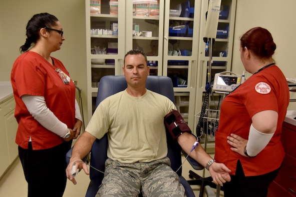 Dee Torres and Barbara Jermyn, Howard College nursing students, practice taking blood pressure and heart rate on Master Sgt. John Gregg, 17th Medical Operations Squadron superintendent, at the Ross Clinic on Goodfellow Air Force Base, Texas, May 2, 2017. Jermyn and Torres came to learn at the clinic as part of two-day clinical rotation partnership with Howard College. (U.S. Air Force photo by Staff Sgt. Joshua Edwards/Released)