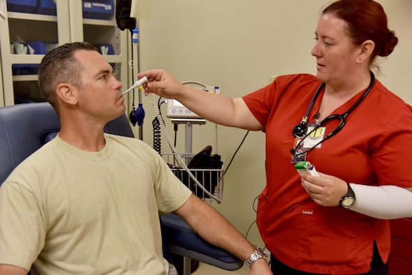 Barbara Jermyn, Howard College nursing student, practices taking a temperature on Master Sgt. John Gregg, 17th Medical Operations Squadron superintendent, at the Ross Clinic on Goodfellow Air Force Base, Texas, May 2, 2017. Jermyn and other Howard College nursing students get a chance to come to base clinic to learn from Goodfellow doctors and nurses. (U.S. Air Force photo by Staff Sgt. Joshua Edwards/Released)