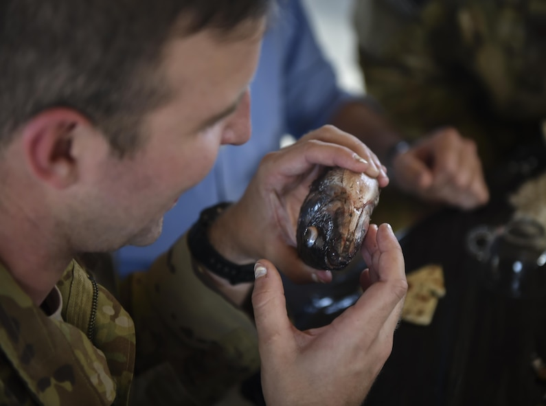 "Capt. Ian Hocking, a combat aviation advisor student with the 6th Special Operations Squadron, holds a fish head during Operation Raven Claw at Duke Field, Fla., April 26, 2017. Students were exposed to ""Palmetto Land"" culture which includes sucking the eyes out of a fish head, eating with their hands and singing karaoke. (U.S. Air Force photo by Airman 1st Class Joseph Pick)"