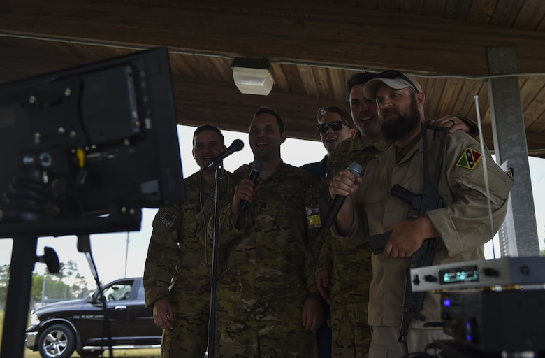 "Combat aviation advisor students with the 6th Special Operations Squadron sing karaoke with ""Palmetto Land"" forces during Operation Raven Claw at Duke Field, Fla., April 26, 2017. Students were exposed to ""Palmetto Land"" culture which includes sucking the eyes out of a fish head, eating with their hands and singing karaoke. (U.S. Air Force photo by Airman 1st Class Joseph Pick)"