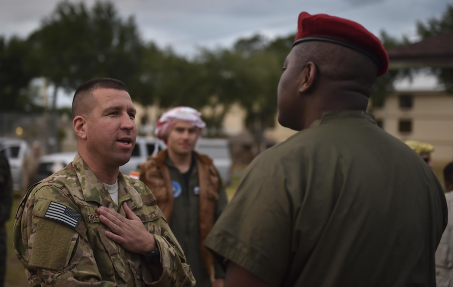 """Lt. Col. Benjamin Griffith, a combat aviation advisor student with the 6th Special Operations Squadron, greets the commander of the """"Palmetto Land"""" forces during Operation Raven Claw at Duke Field, Fla., April 26, 2017. Students were exposed to """"Palmetto Land"""" culture which includes sucking the eyes out of a fish head, eating with their hands and singing karaoke. (U.S. Air Force photo by Airman 1st Class Joseph Pick)"""