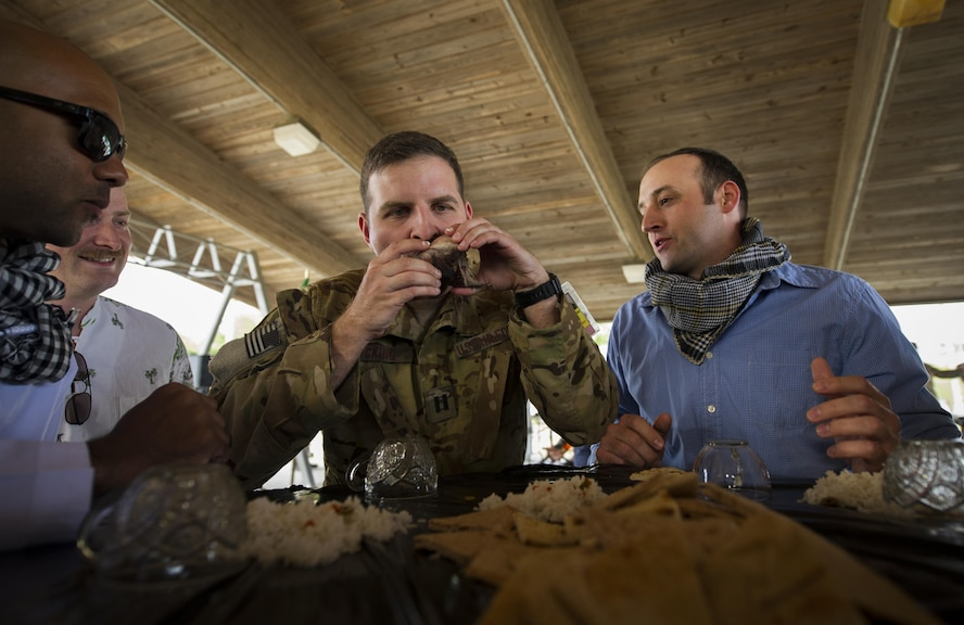 "Capt. Ian Hocking, a combat aviation advisor student with the 6th Special Operations Squadron, sucks the eyes out of a fish head during Operation Raven Claw at Duke Field, Fla., April 26, 2017. Students joined their partners in a meal that is considered a luxury in ""Palmetto Land"" culture to strengthen relationships. (U.S. Air Force photo by Airman 1st Class Joseph Pick)"