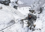 Army Pfc. Olivia French, a medic with the 7th Engineer Battalion, 10th Mountain Division, climbs the mountain at Smugglers' Notch in Jeffersonville, Vt., Feb. 18, 2016. The Mountain Walk is a culminating event for basic and advanced mountain warfare students to use the skills taught at the Army Mountain Warfare School at the Camp Ethan Allen training site. Air Force photo by Tech. Sgt. Nathan Rivard