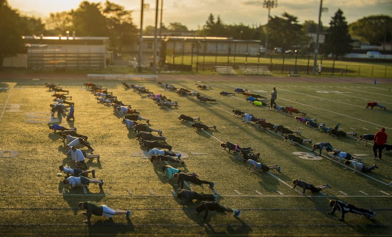 Participants of the Warrior Run fitness program perform push-ups April 28, 2017, at Yokota Air Base, Japan. The Warrior Run currently has about 115 participants during the morning session and about 30 participants during the afternoon session. (U.S. Air Force photo by Airman 1st Class Donald Hudson)