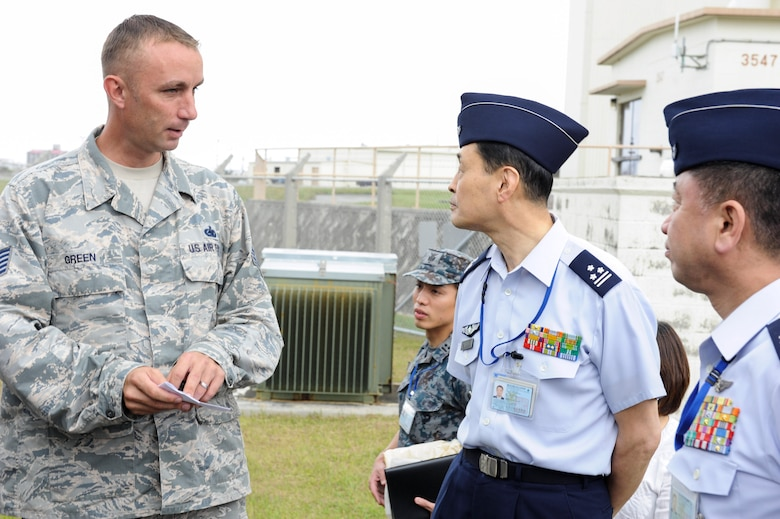 U.S. Air Force Tech. Sgt. Jeffrey Green, 18th Logistics Readiness Squadron fuels facilities NCO in charge, speaks with Japan Air Self-Defense Force Col. Riichi Furugaki, JASDF Air Staff College director of education department, and JASDF Col. Tooru Oota, JASDF Air Staff College head of education section, April 27, 2017, at Kadena Air Base, Japan.  Japan Air Self-Defense Force Air Staff College members were invited to see the different fuel capabilities of the 18th LRS petroleum, oils and lubricants flight, share information and ask questions. (U.S. Air Force photo by Senior Airman Lynette M. Rolen)